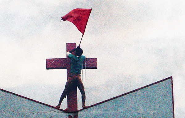 Contested territory: a Hindu nationalist raises a saffron flag atop a church in Muniguda in India's Orissa state. Minority communities in India are regularly targeted by politically instigated Hindu groups, and churches have been burned and defaced.